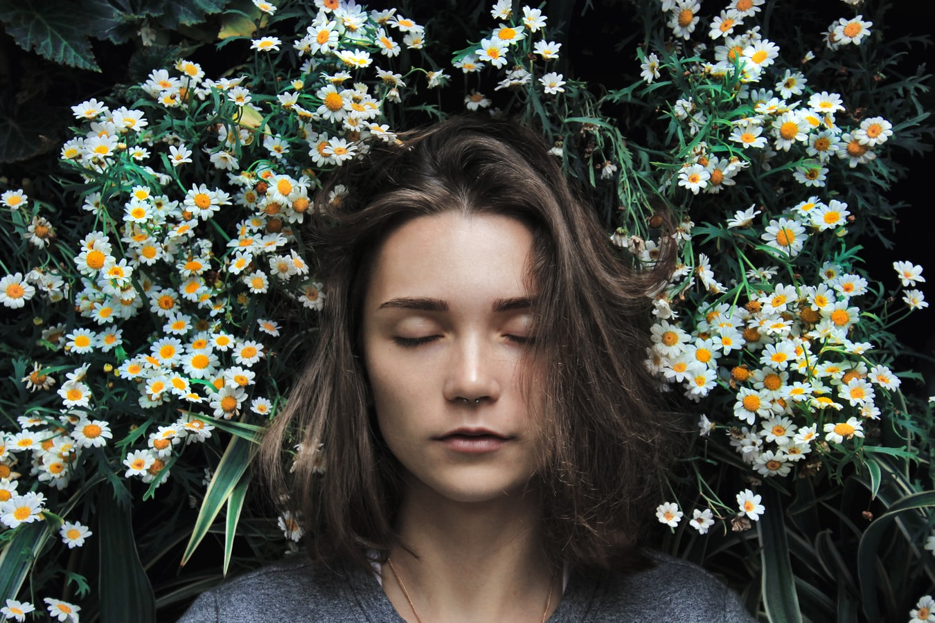 girl with closed ones surrounded by small white flowers